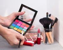 Cepillos, sombras, barras de labios y esponjas cosméticos profesionales en una tabla gris imágenes de archivo libres de regalías