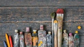 Cepillos, tubos con la pintura y lápices coloreados fotos de archivo