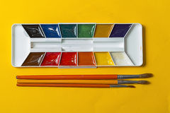 Cepillos y acuarelas en un fondo amarillo Fotografía de archivo
