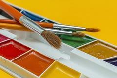 Cepillos y acuarelas en un fondo amarillo Fotos de archivo libres de regalías
