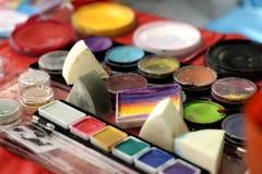 cepillos y colores de la Cara-pintura Fotos de archivo