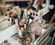 Cepillos y cosmético del maquillaje en el tocador Foto de archivo