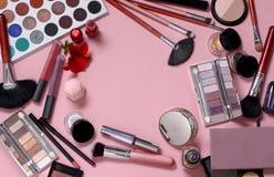 Cepillos y cosm?ticos del maquillaje en un fondo rosado imagen de archivo