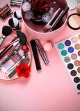 Cepillos y cosm?ticos en un fondo rosado, caja de almacenamiento del maquillaje foto de archivo