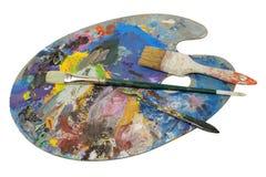 Cepillos y cuchillo del ` s del pintor en la paleta usada Imágenes de archivo libres de regalías