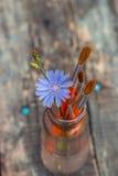 Cepillos y flor en un tarro de cristal en el tablero Imagenes de archivo