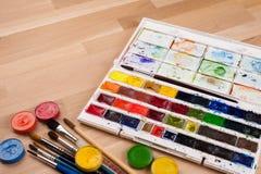 Cepillos y fuentes del arte en la tabla de madera Fotos de archivo libres de regalías