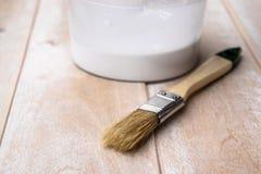 Cepillos y latas con la pintura blanca en los tableros Preparaci?n para los tableros de pintura imágenes de archivo libres de regalías