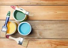 Cepillos y latas de la pintura en fondo de madera, Fotos de archivo libres de regalías