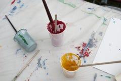 Cepillos y pinturas de pintura en la mesa de trabajo Imagen de archivo libre de regalías