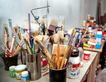 Cepillos y pinturas en el estudio del artista Fotos de archivo libres de regalías
