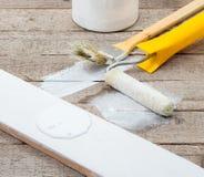 cepillos y rodillos para pintar tablones de madera imagenes de archivo