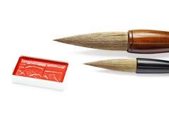 Cepillos y tinta de escritura asiáticos para la caligrafía aislados en blanco imagenes de archivo