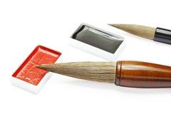 Cepillos y tinta de escritura asiáticos para la caligrafía aislados en blanco fotografía de archivo
