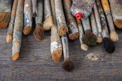 Cepillos y tubo viejos con la pintura imagenes de archivo