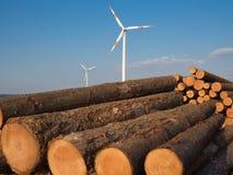 Ceppi di legno del mucchio con un generatore eolico Immagine Stock