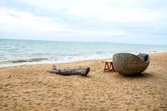 Ceppo di legno e sedia di vimini sulla spiaggia fotografie stock