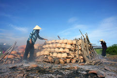 Cerámica de la quemadura de la gente al aire libre en la tierra. PHAN CORRIÓ Imagen de archivo