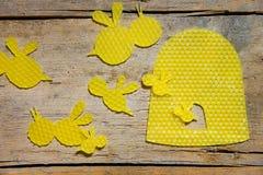 Cera de abejas, abejas y una colmena en la tabla de madera Imagenes de archivo