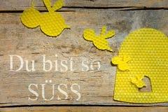 Cera de abejas, abejas y una colmena en la tabla de madera, texto alemán, concep Fotos de archivo libres de regalías