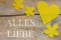 Cera de abejas, corazón y flores en la tabla de madera, palabras alemanas, amor Imágenes de archivo libres de regalías