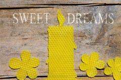 Cera de abejas, vela y flores en la tabla de madera, sueños dulces Fotografía de archivo