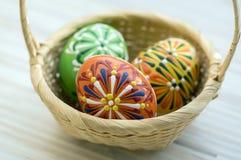 A cera três pintou ovos da páscoa na luz - cesta de vime marrom Fotos de Stock Royalty Free