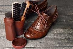 Cera y cepillos del zapato en superficie de madera Fotos de archivo libres de regalías