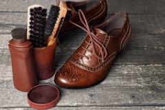 Cera y cepillos del zapato en superficie de madera Imagen de archivo