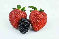 An cereal delight,. Two strawberries and a raspberries on a white back ground Stock Photography