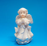 Ceramic angel on blue background Stock Photos