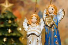 Ceramic angel toys and christmas tree. Ceramic angel toys hanging against colorful background Royalty Free Stock Images