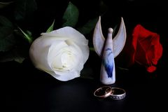 Wedding rings, angel figure, white and red roses on black background. Symbolic concept — love, loyalty, wedding, family, royalty free stock photo