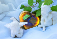 2 Ceramic Angles on White Clouds. 2 cherubs sitting on a fluffy white material with colorful heart and birch leaves Stock Image