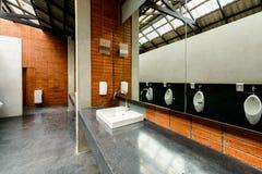 Ceramic bathroom sink in men`s bathroom. White ceramic bathroom sink in men`s bathroom stock image