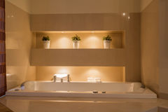 Ceramic bathtub in illuminated bathroom Stock Images