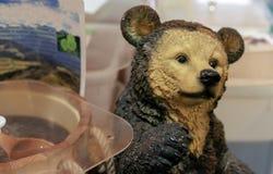 Ceramic bear figurine next to a barrel of honey stock photo