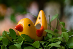 Ceramic bird on green leaves. Stock Image