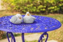 Ceramic birds on blue table. Decorative ceramic birds on top of blue iron table Royalty Free Stock Photo