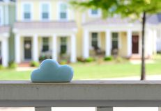 Ceramic blue cloud. Sitting on white fence Stock Photos