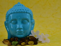 Ceramic Blue color Serene face statue of Buddha with flowers  on colorful yellow background Stock Photography