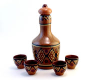 Ceramic bottle with small ceramic cups. Covered with ornament Royalty Free Stock Photos