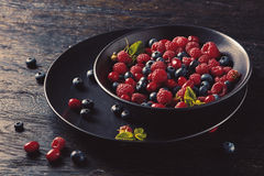 Ceramic bowl with assortment berries. Bowl with assortment berries with mint at black wooden table Stock Image