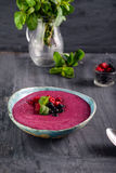 Ceramic bowl with berry smoothie decorated with currant, raspberry and mint on the black wooden background - Well being, Healthy e. Ating, Detox or Diet concept Stock Photos