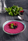 Ceramic bowl with berry smoothie decorated with currant, raspberry and mint on the black wooden background - Well being, Healthy e. Ating, Detox or Diet concept Royalty Free Stock Image