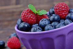 Ceramic bowl with blueberries and raspberries. On table Stock Images