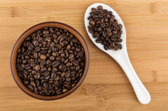 Ceramic bowl with coffee beans and white spoon on table Royalty Free Stock Photo
