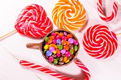 Ceramic bowl with colored candies and lollipops on a wooden table. Top view royalty free stock photography