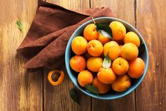 Ceramic bowl of fresh harvested apricots over wooden table. Selective focus Royalty Free Stock Images
