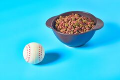 Ceramic bowl full of dry food for pet near baseball ball on blue background